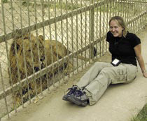 Myriah, who lived in Sadam Hussein's palace compound while in Iraq, poses with one of the lions kept by Hussein